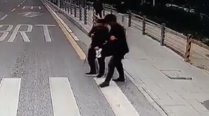 暖!盲人过斑马线踟蹰不敢走 公交司机立刻下车扶其过街