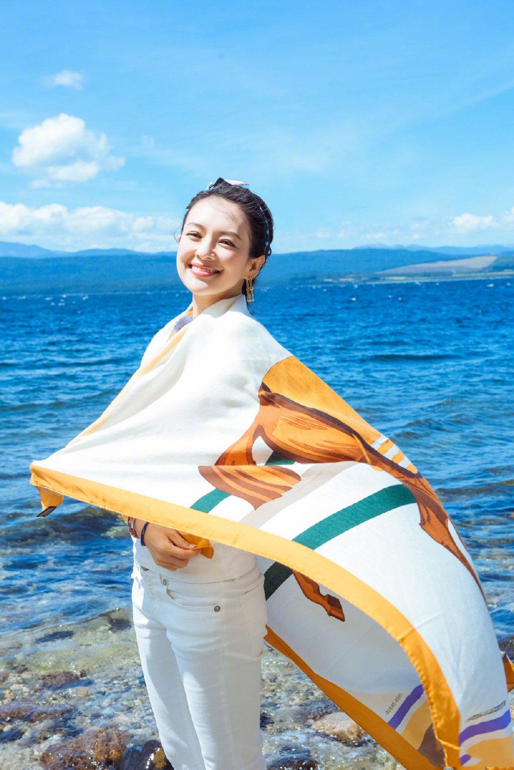 章子怡身穿白色休闲装搭配亮色披肩,优雅又不失活力。
