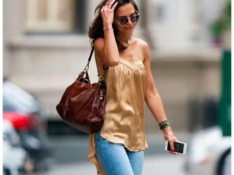 女星凯蒂·霍尔姆斯深金色吊带上衣搭配牛仔裤亮相街头,长发很飘