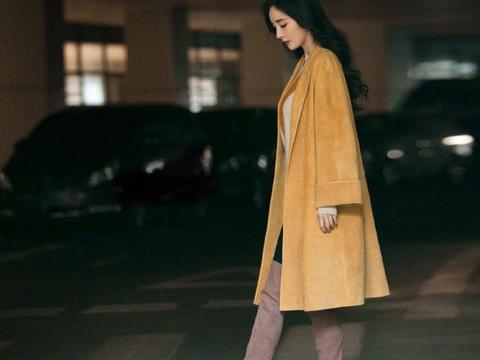 杨幂真会打扮,姜黄色大衣内搭毛衣亮相,大波浪卷发配长筒靴好美