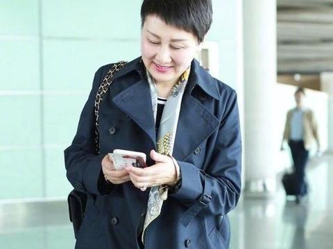 57岁张凯丽状态真好,穿深蓝色风衣配短发走机场,丝巾太有品味