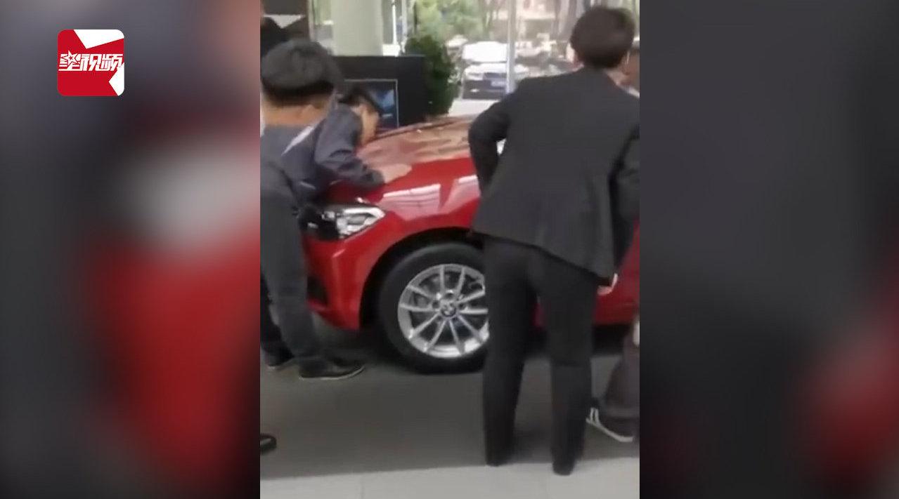 视频:尴尬!宝马女车主坐引擎盖维权,工作人员发现车盖被坐瘪