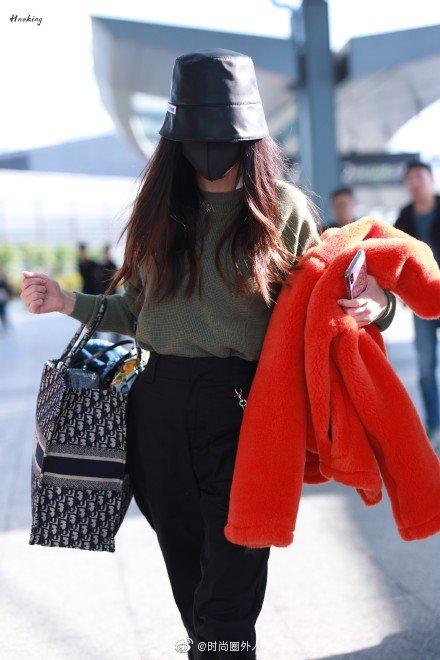 戴着口罩帽子全幅武装现身机场,自提行李,看上去心情很不错。