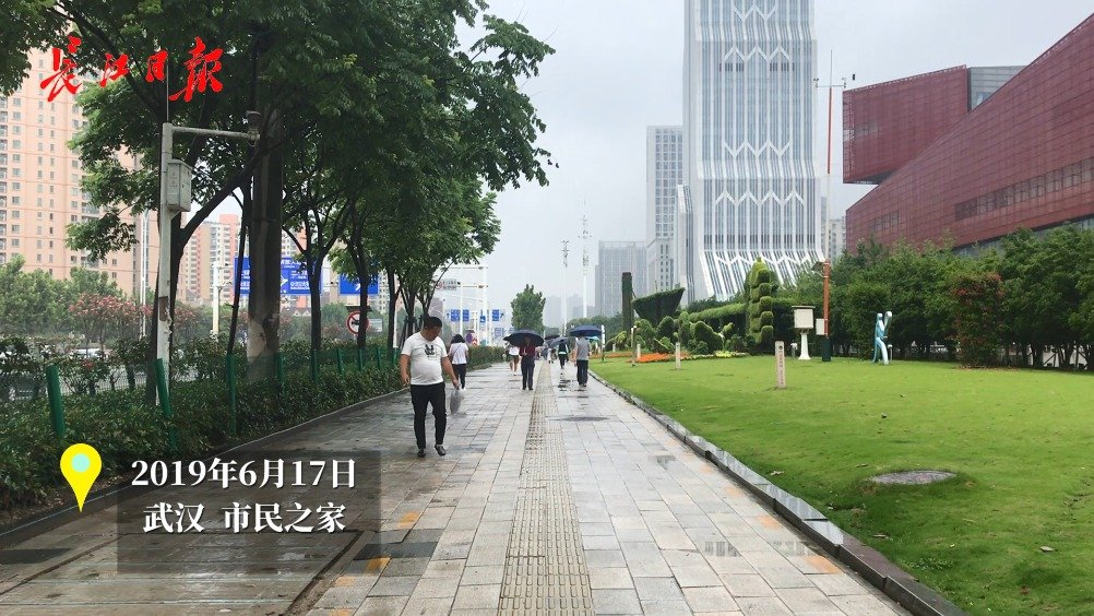 武汉梅雨季第一天:地铁口挤满躲雨人群,有人头顶塑料袋上班