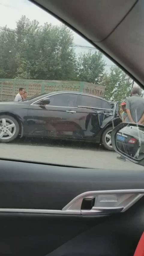 网爆万昌路口这辆黑色私家车被大车追尾,三厢变两厢太惨了