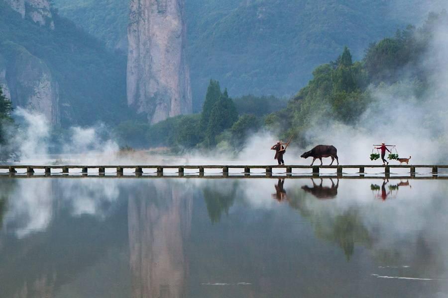 浙江仙都空手把锄头,步行骑水牛。人从桥上过,桥流水不流。