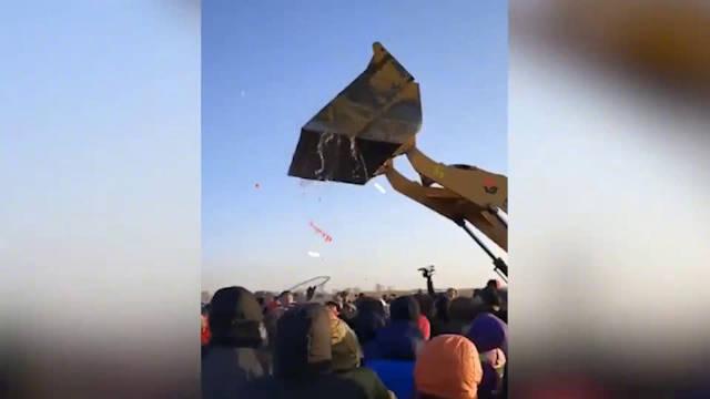 黑龙江一景区用铲车空中洒鱼 千名游客疯抢