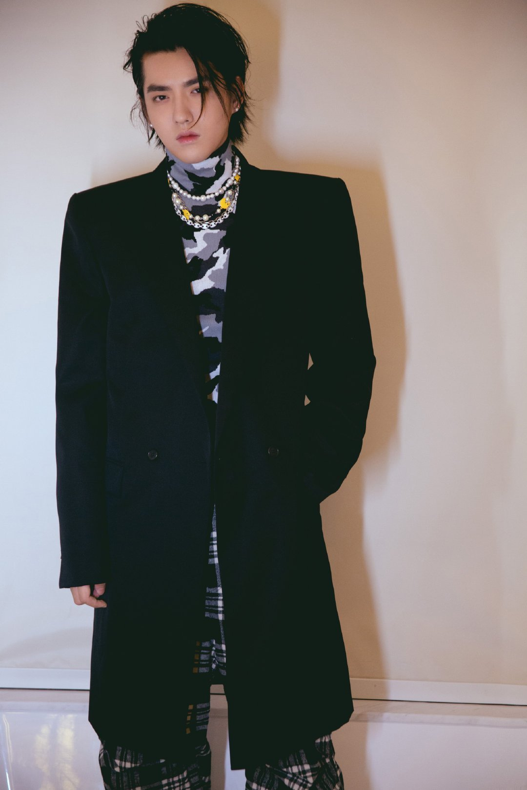 吴亦凡身穿大廓形西服搭配同系列的迷彩高领针织衫、格纹阔腿裤亮相汽