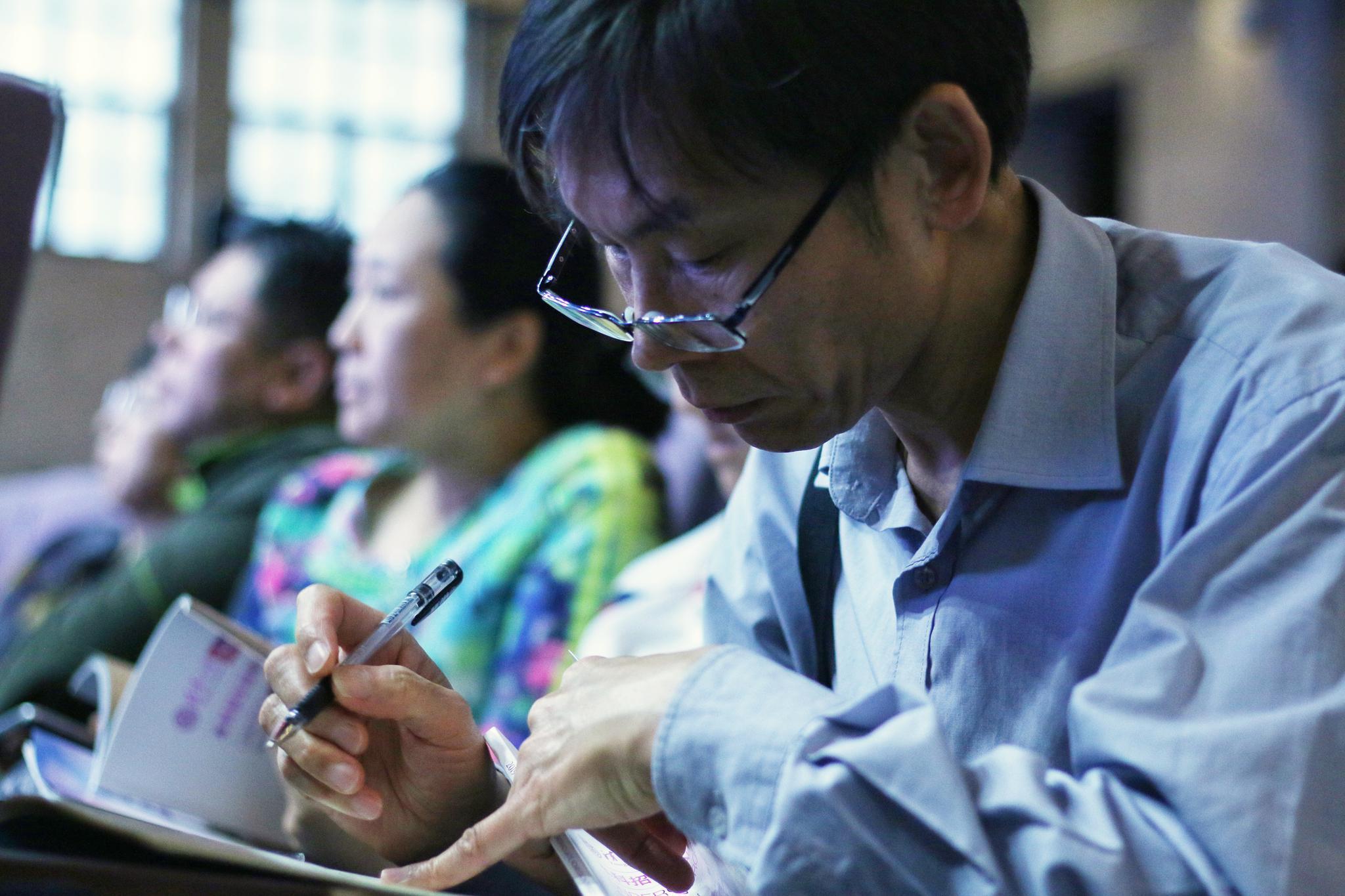 一位家长在清华大学大礼堂记录招生信息。摄影/新京报记者陈婉婷