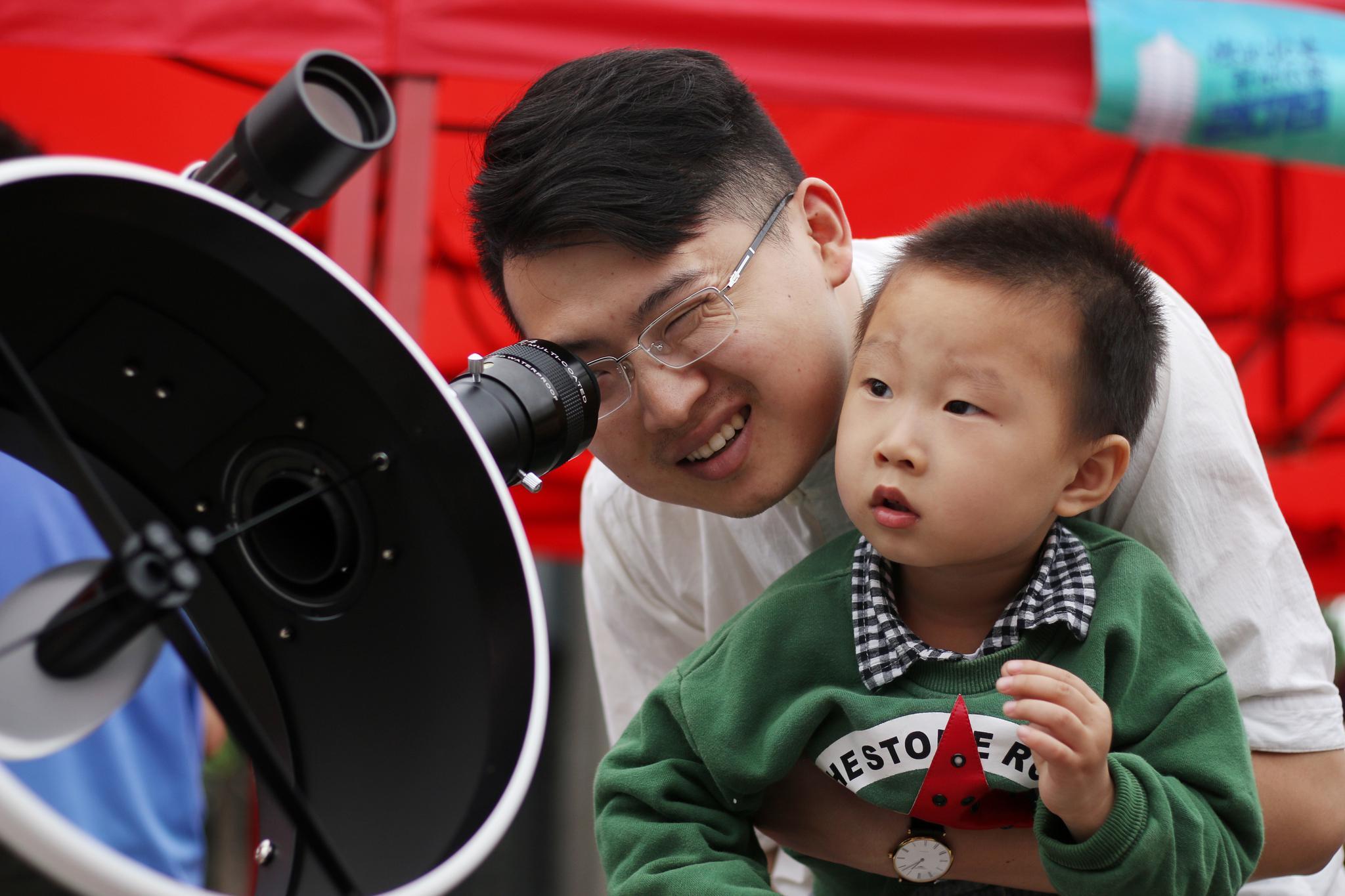 青年天体学会前,参观者通过十二寸道布森式望远镜看远处。摄影/新京报记者陈婉婷