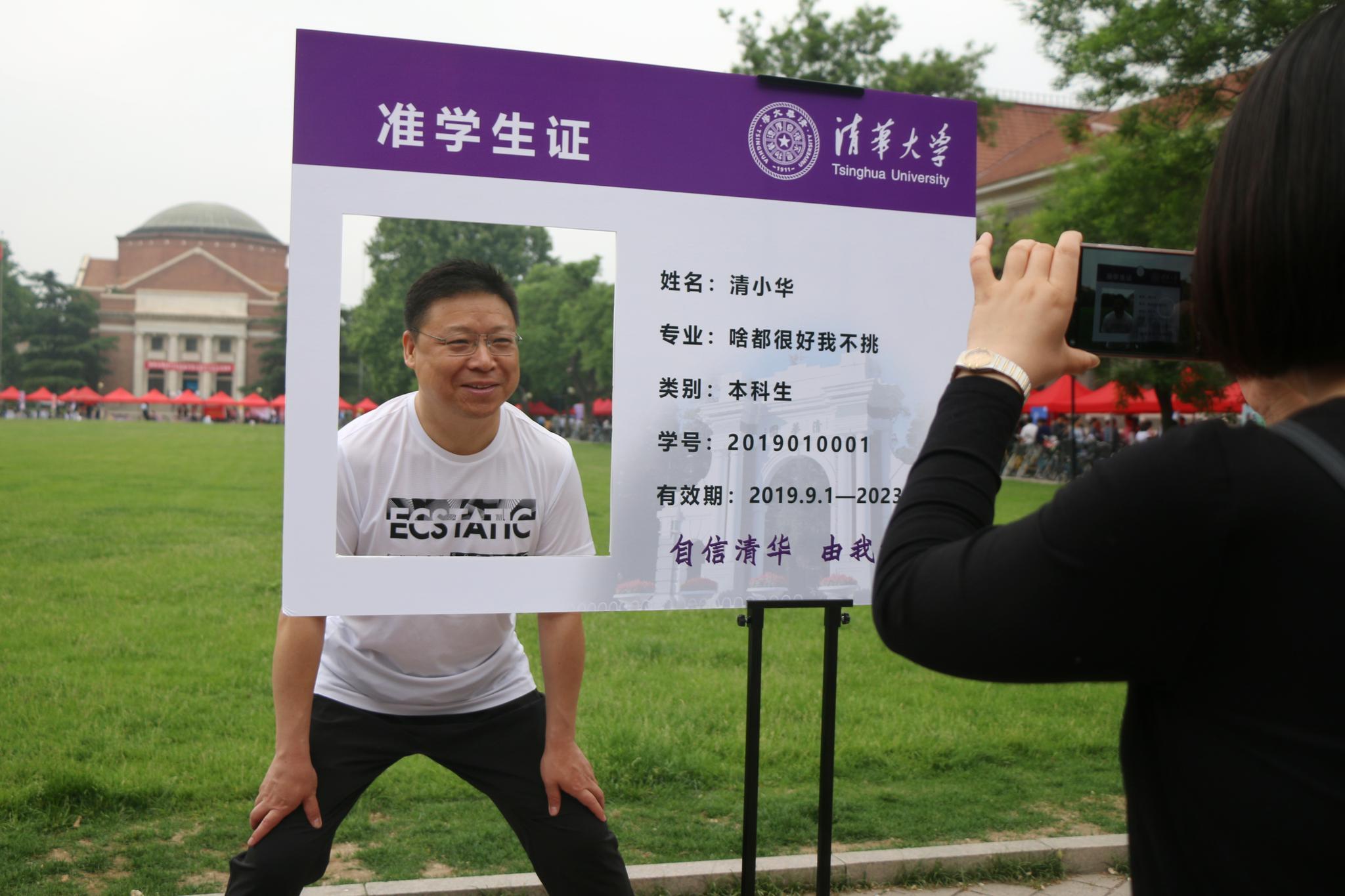 今天上午,一位家长在清华大学大礼堂前合影留念。摄影/新京报记者陈婉婷