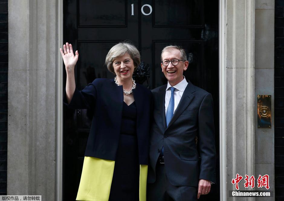 資料圖:當地時間2016年7月13日,英國新首相特蕾莎·梅與丈夫菲利普正式入主唐寧街10號,同時,她任命的新內閣核心成員也都悉數露面。圖爲特蕾莎夫婦。