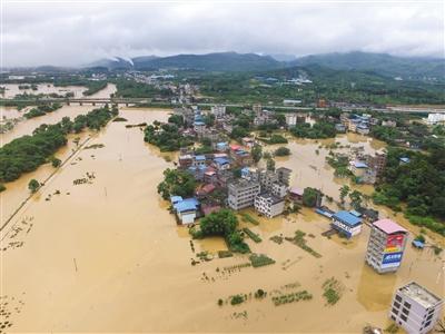 6月9日,广西桂林,全州县遭受洪水袭击,沿江两岸房屋、公路、村庄、农田被洪水淹没,当地政府及时启动防汛预案进行防洪抢险工作。图/视觉中国