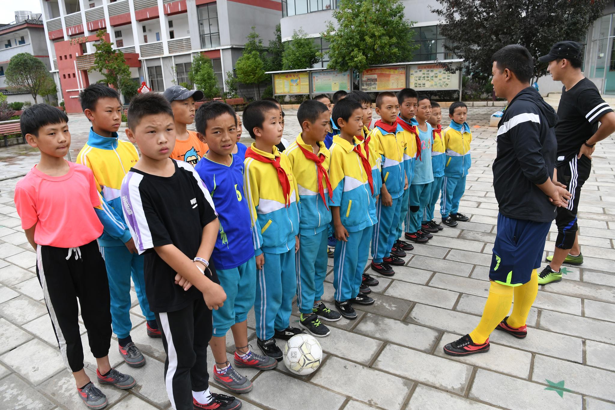 """北京的职业足球教练给""""追风""""少年带来了足球装备与技术"""