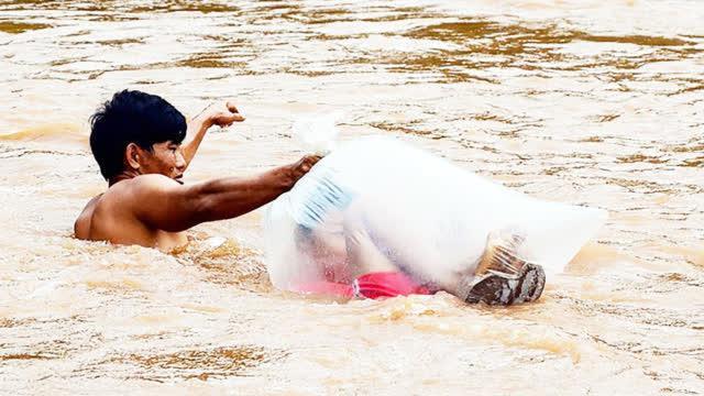 心酸!越南洪水泛滥河流齐脖深 家长用塑料袋运孩子过河上学