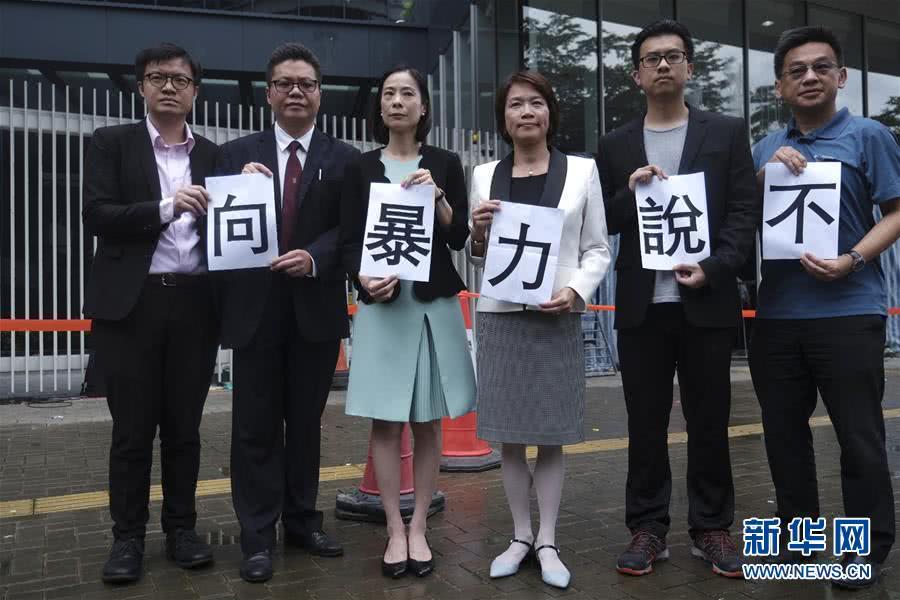 """7月3日,香港特区立法会,香港法律界人士手拿""""向暴力说不""""的纸张谴责暴力行径 图自新华社"""