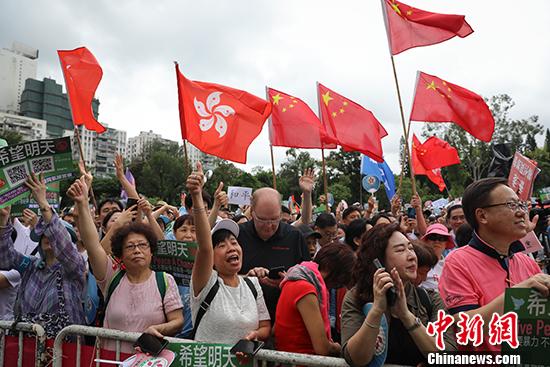 """8月3日,團體""""香港政研會""""下午3時在維多利亞公園草地舉行""""希望明天""""反暴力音樂會,表達對警隊的支持。圖爲現場聚集大批民衆,高呼口號,支持香港警察,支持特區政府。隨處可見中華人民共和國國旗和香港特別行政區區旗迎風飄揚。 中新社記者 謝光磊 攝"""