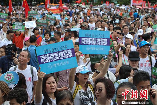 """8月3日,團體""""香港政研會""""下午3時在維多利亞公園草地舉行""""希望明天""""反暴力音樂會,表達對警隊的支持。圖爲現場聚集大批民衆,不少市民拿起""""同聲同氣撐警察""""橫幅,衆人一起爲警察加油,希望香港警察撐下去,保護香港。 中新社記者 謝光磊 攝"""