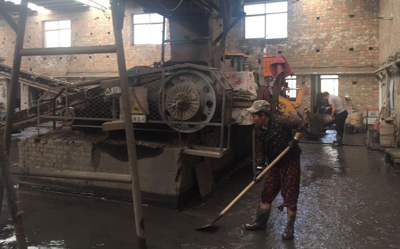 8月2日,桃树洼村第三砖厂的工人正在清理厂房的淤泥。 新京报记者 张胜坡 摄