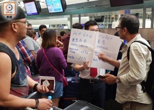 航空公司职员举着写有航班信?⒌闹脚铺嵝崖每? 图源:东网