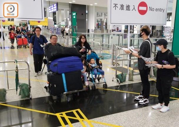 戴口罩的黑衣人向到港旅客发传单 图源:东网