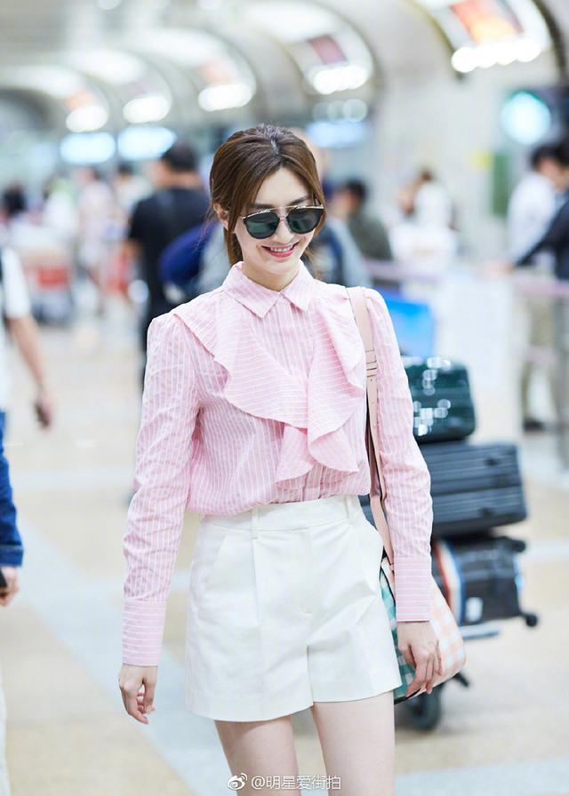 江疏影早前机场照,粉色条纹荷叶边衬衫搭白色短裤,浑身白的发光