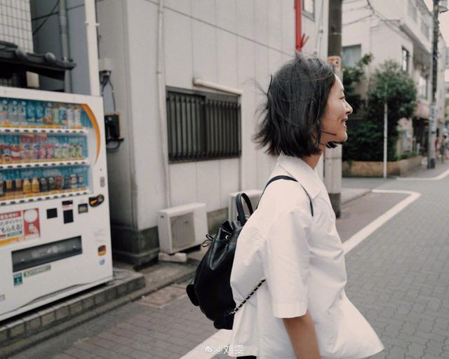 刘雯最新街拍,白色宽松衬衫搭黑色半身裙,黑色背包,高中学生范