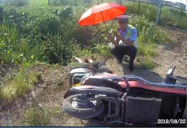 醉汉骑车去钓鱼,途中摔倒水边昏迷不醒,民警为他打伞遮阳
