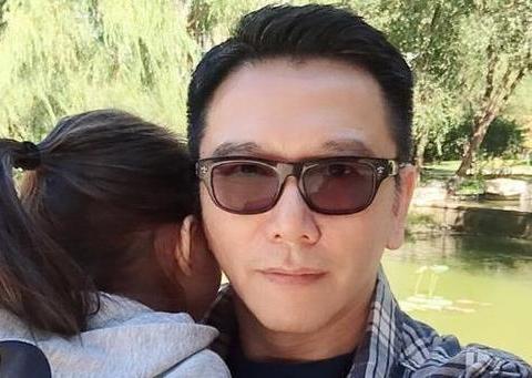 54岁温兆伦带女儿出游,3岁女儿玩累伏在肩头睡,父女同框显温馨