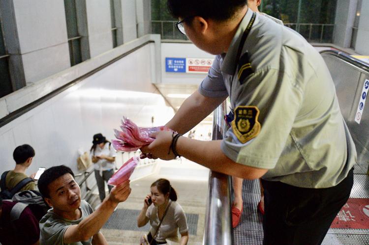 惠新西街南口地鐵站,工作人員爲出站乘客分發一次性雨衣。