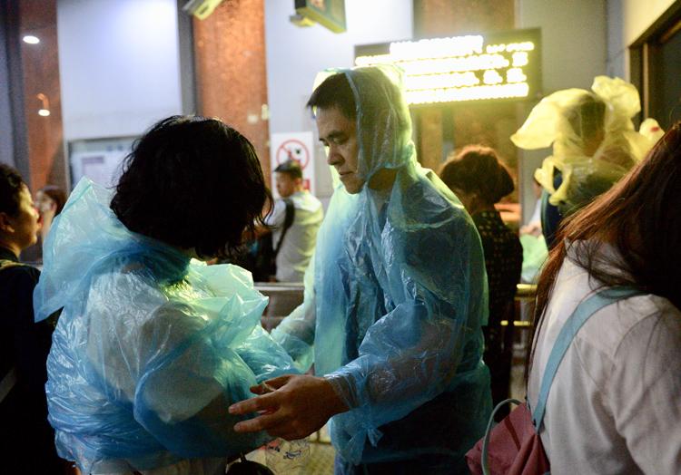 9月9日晚,惠新西街南口地鐵站,一名乘客幫家人穿好雨衣。