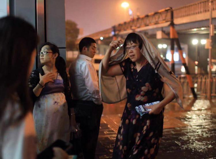 市民在地鐵站出口處等雨停。