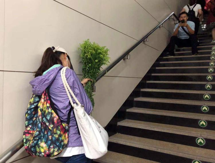 未帶雨具的市民在地鐵站出口處躲雨。
