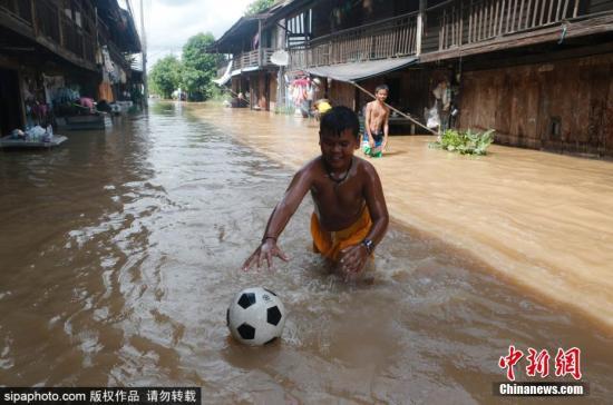 本地工夫9月3日,泰国披散府,男孩们正在被大水吞没的菲契特街上玩足球。图片滥觞:Sipaphoto 版权做品 制止转载