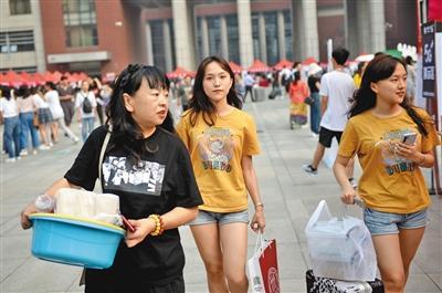 报到完的新生与家人带着行李前往宿舍。