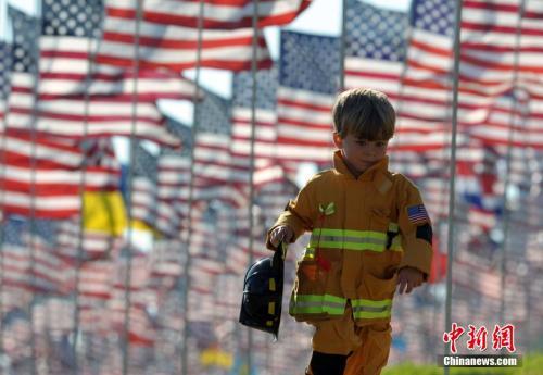 资料图:一名身着消防员服装的儿童从美国国旗下跑过。 中新社发 毛建军