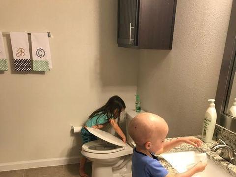 一位美国妈妈分享一张让人心碎的照片:5岁女儿照顾2岁生病的弟弟