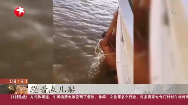 哈尔滨:市民松花江中游泳遇险  海事船员搭救