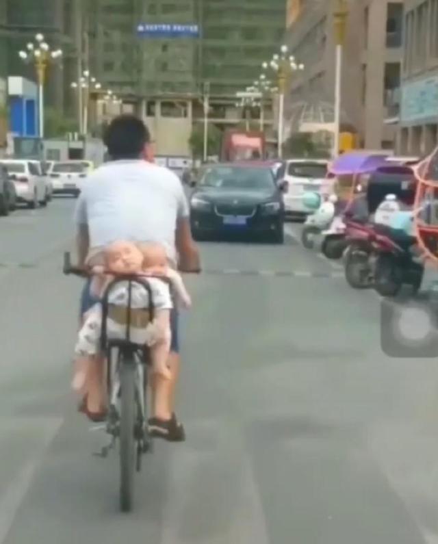 爸爸骑自行车带双胞胎,宝宝们在后座打瞌睡,网友笑称:活着就好