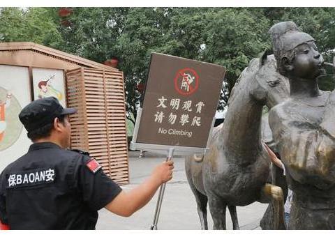 游客攀爬景区雕塑拍照,保安喊话劝告无效,沉默地递上一牌子