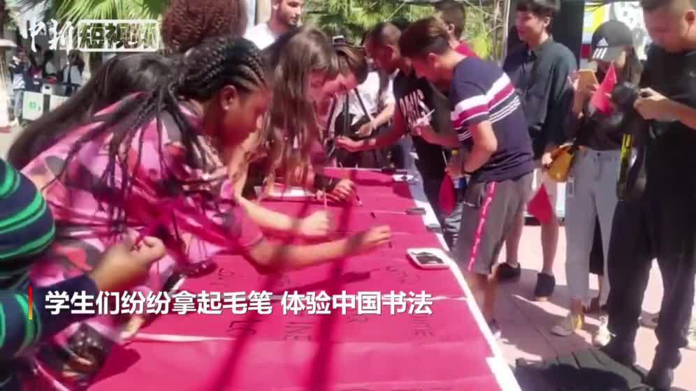 """外籍留学生用毛笔书写""""我爱中国"""""""