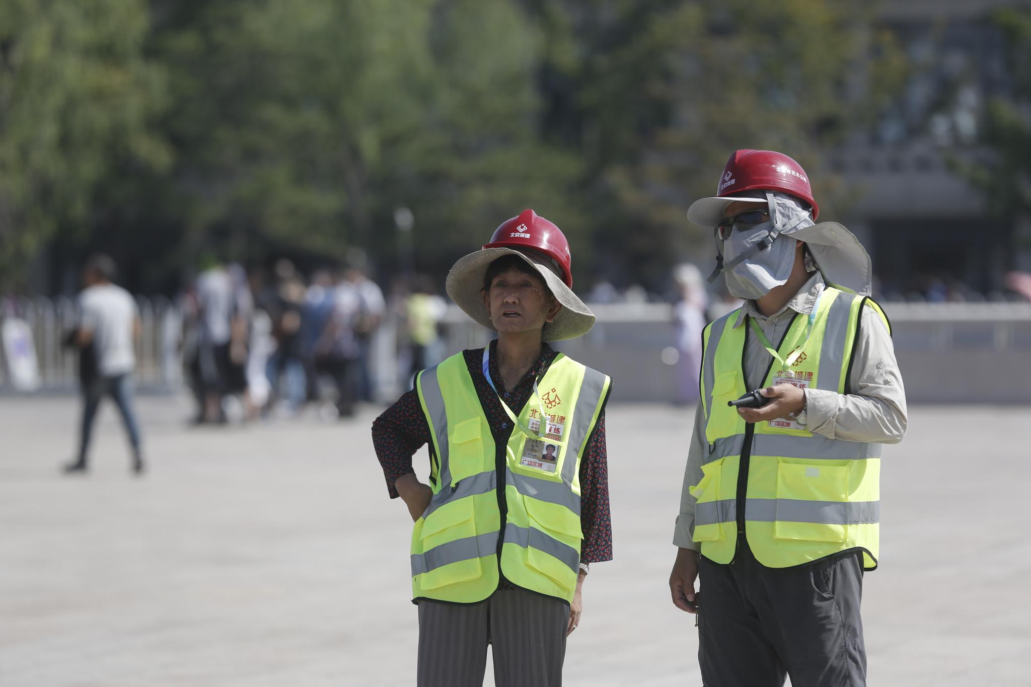花篮设计师王绥枝(左)也在现场参与搭建工作。摄影/新京报记者 侯少卿