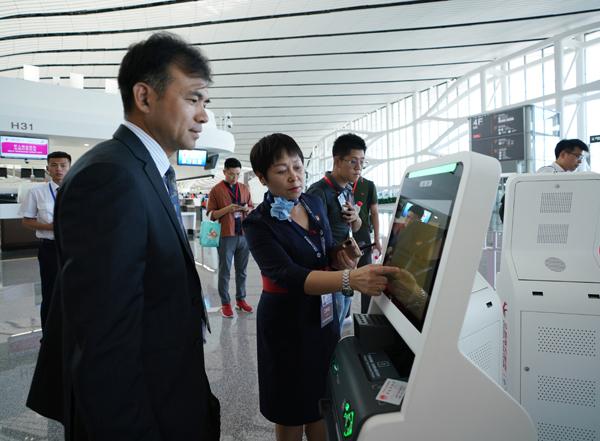 """9月25日,中国西方航空公司事情职员(前左两)正在指点搭客经由过程""""人脸辨认""""打点值机脚绝。"""