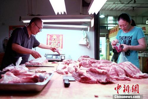 材料图:公众于菜市场内购置猪肉。中新社记者 张近 摄