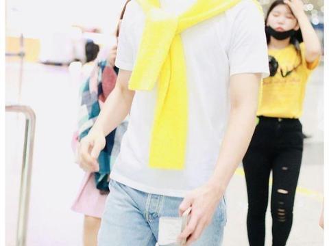 男演员现身机场,穿白T恤搭黄色针织衫,踩小白鞋演绎元气大男孩