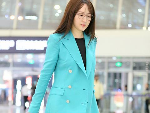 48岁杨钰莹素颜走机场 穿蓝色西装知性大方 拿书本娇羞挡脸