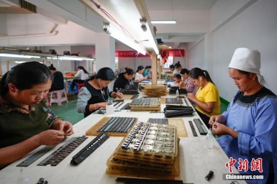 资料图:民众在一处扶贫车间工作。中新社记者 贺俊怡 摄