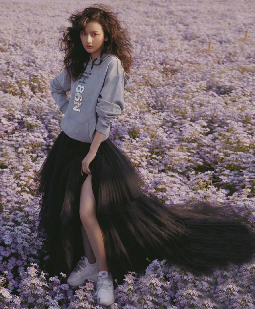 宋祖儿一头复古卷发,配高开叉轻纱蛋糕裙,站紫色花海中美成精灵