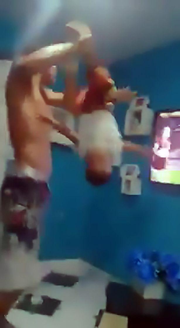 英国球迷在球星巴博萨进球时,激动地抓住儿子脚踝在空中来回晃动