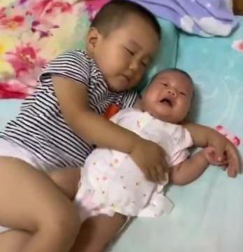 哥哥帮妈妈哄妹妹睡觉,结果成功哄睡自己,妈妈看到后哭笑不得